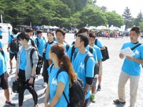 (3)泉ゼミの学生たちと後ろから声を掛ける泉先生、各自の背中には救護用具のバッグが